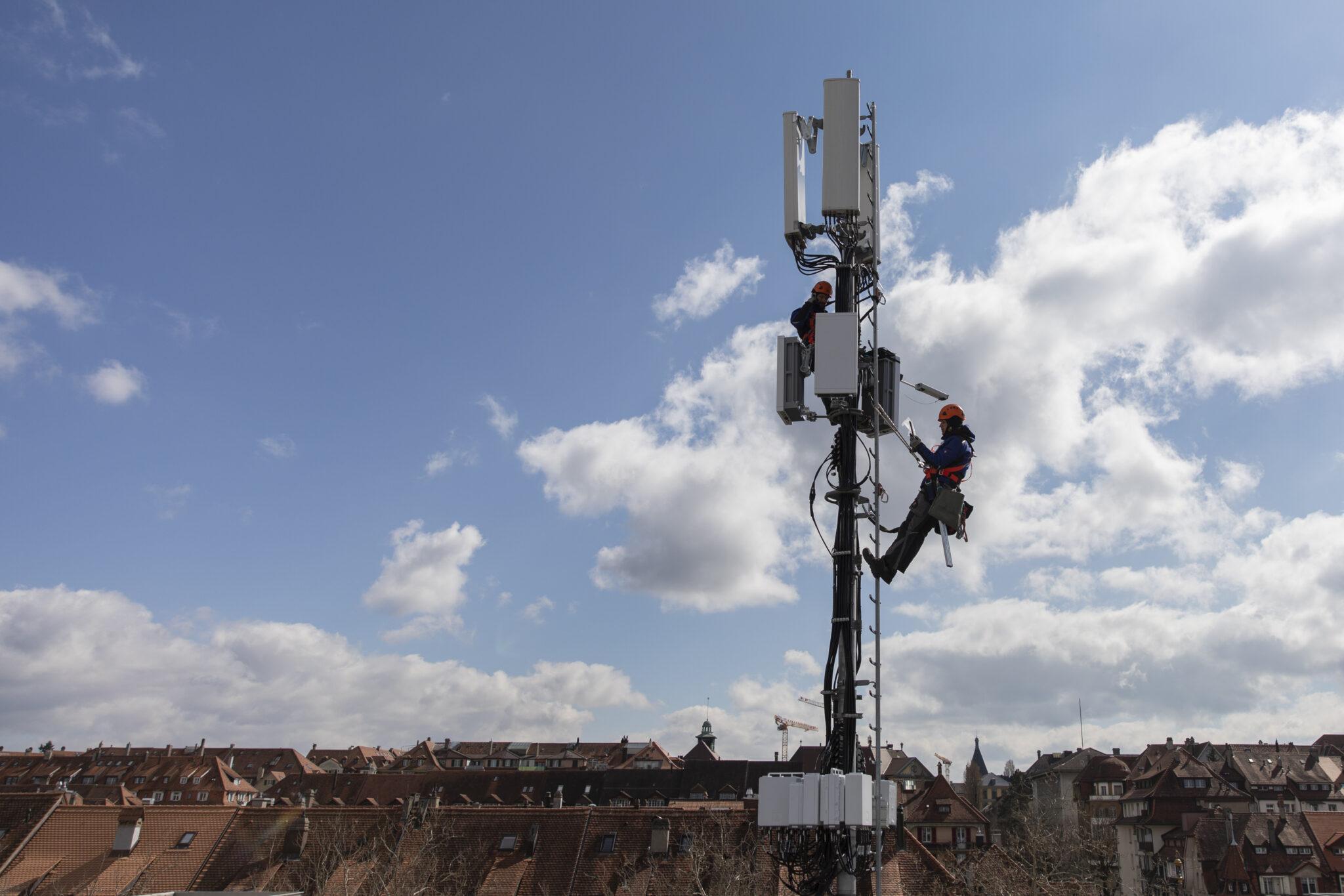 Mann hängt an 5G-Antenne