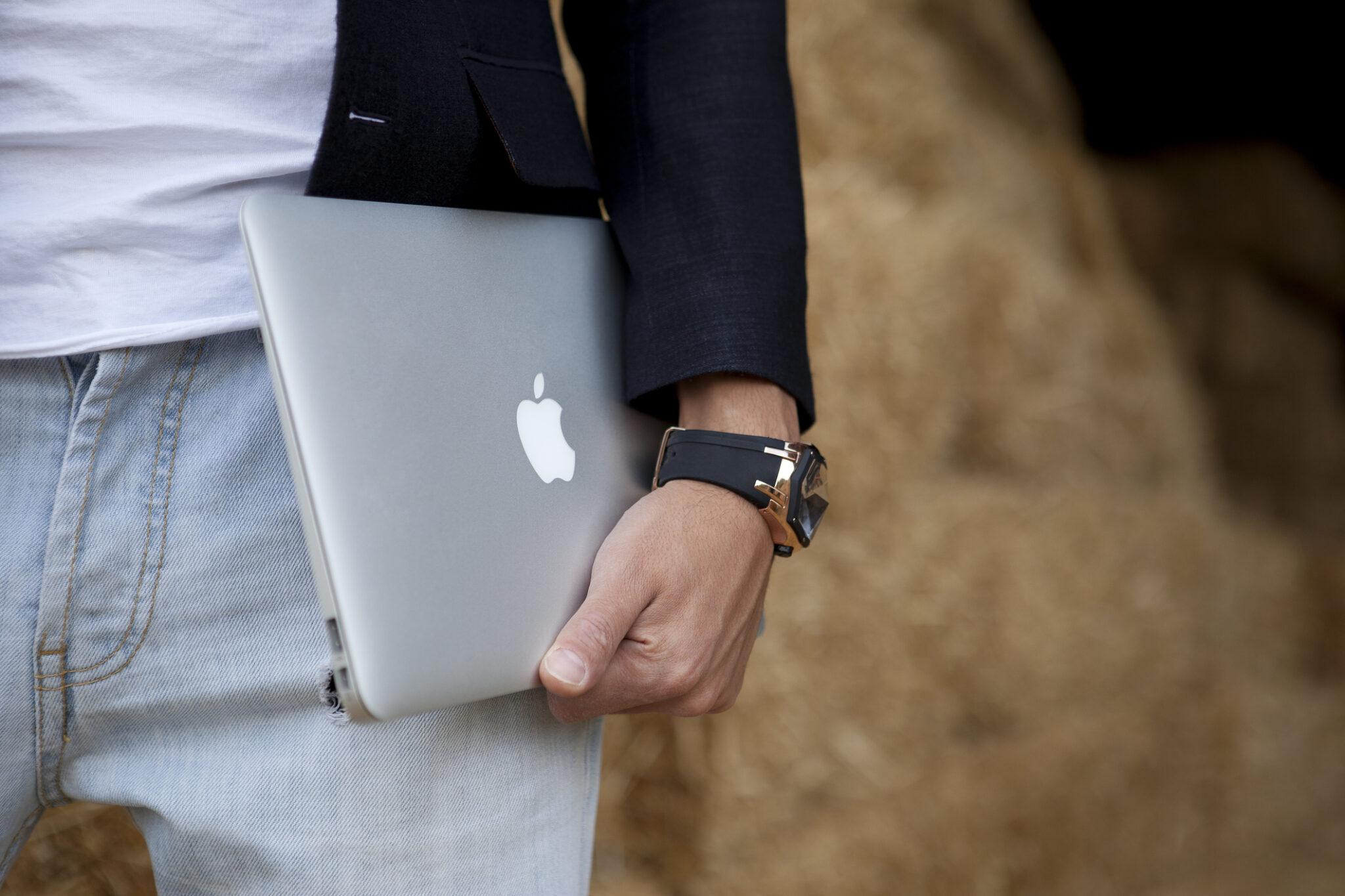 Mann mit MacBook in der Hand