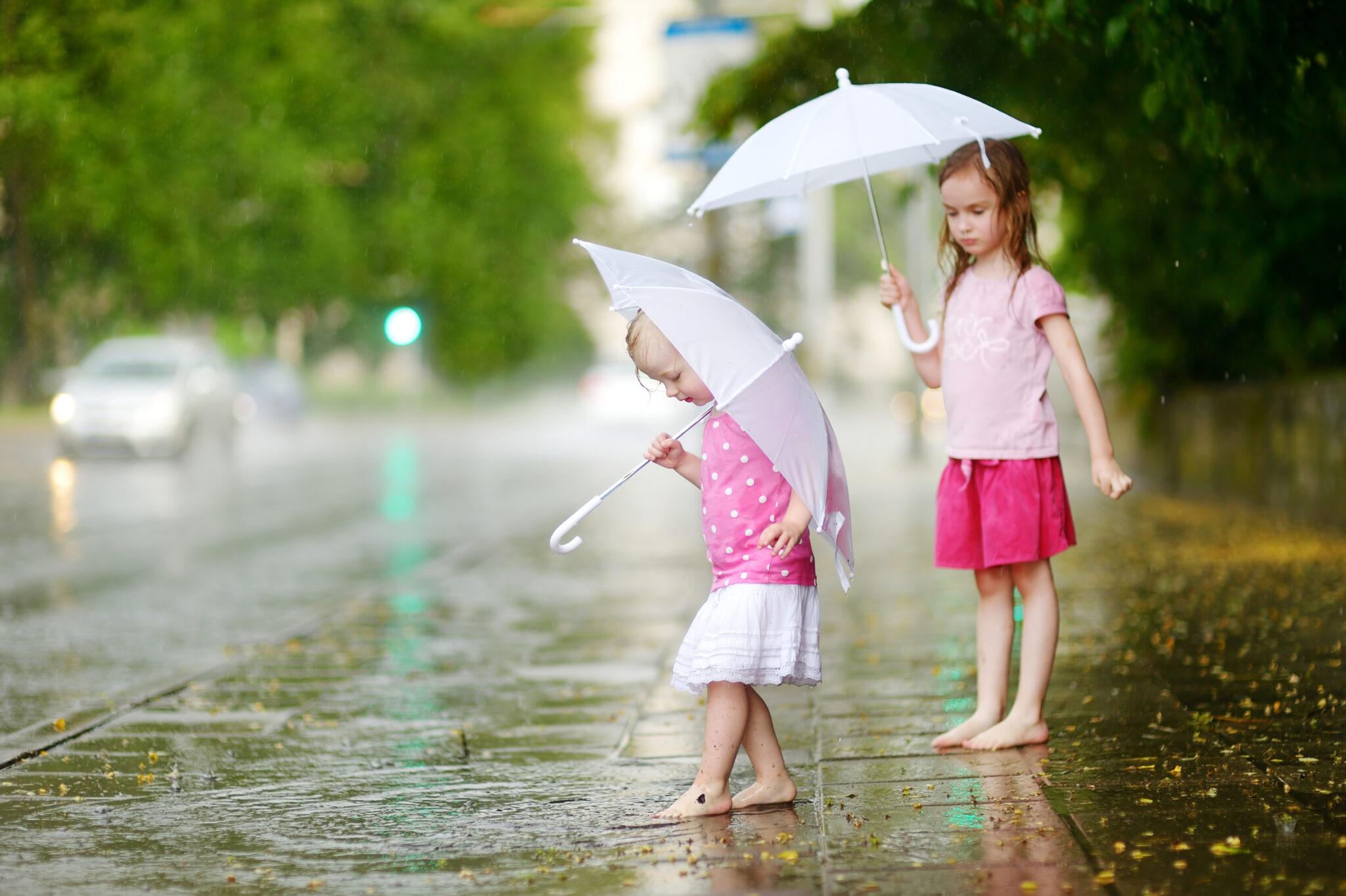 Zwei Mädchen mit Regenschirmen