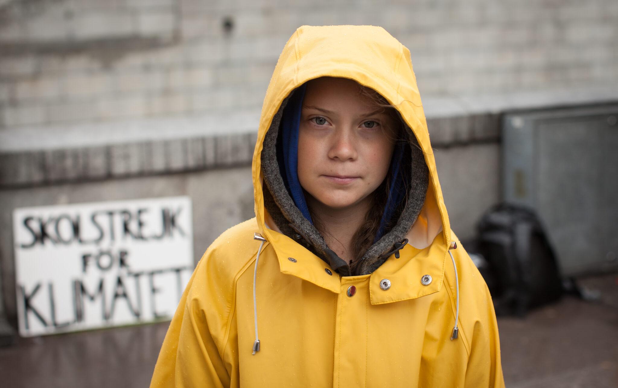 """Greta Thunberg in gelber Regenjacke. Im Hintergrund ihr Schild """"skolstrejk för klimatet"""""""