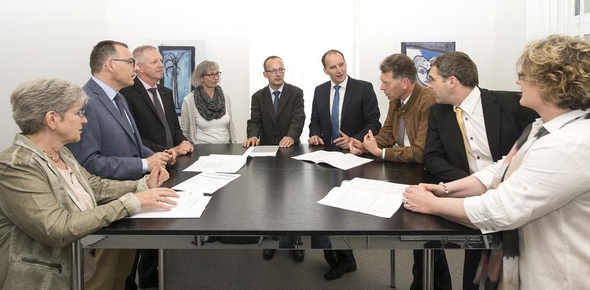 Drei Frauen und sechs Männer an einem Tisch