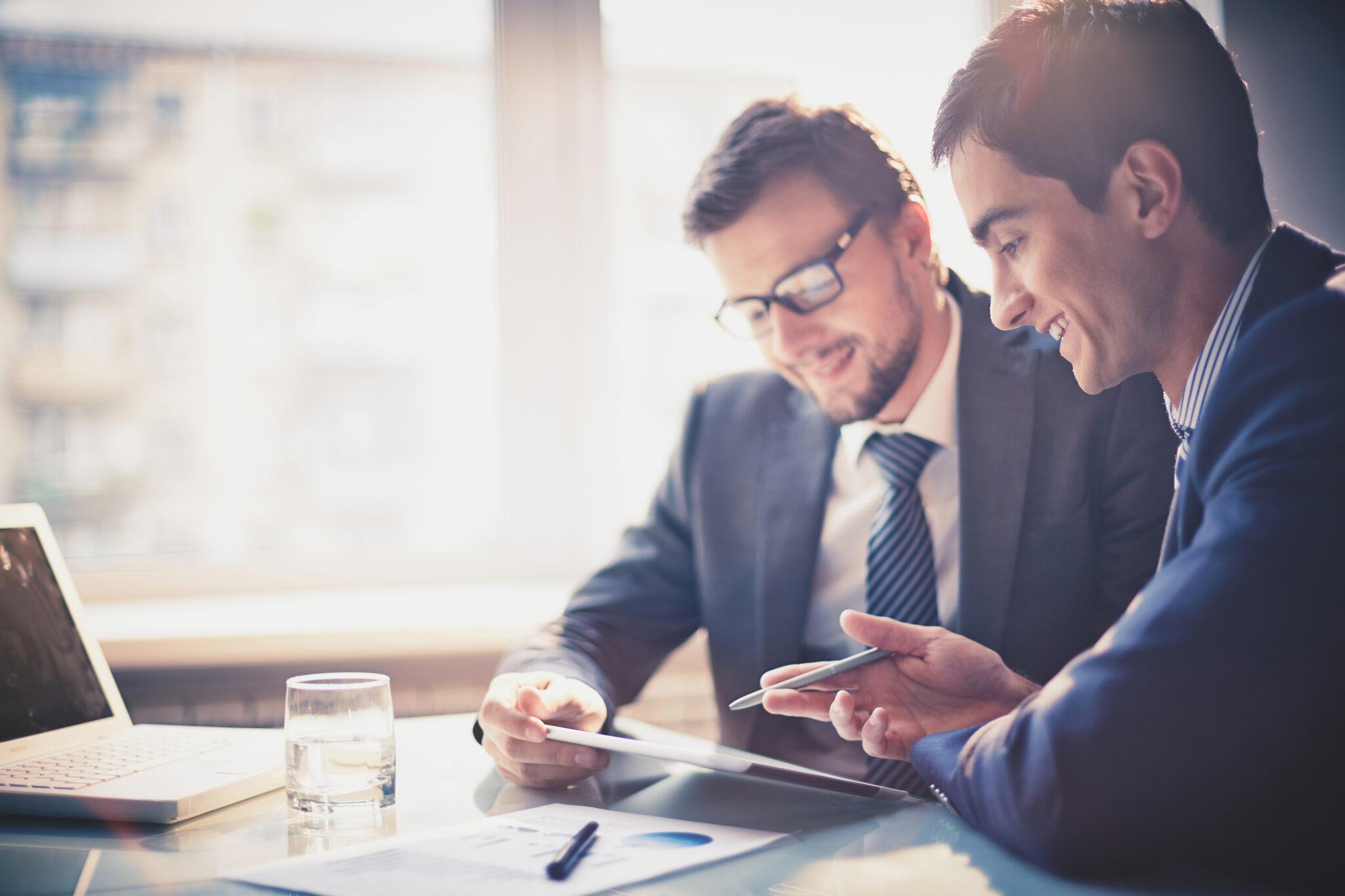 Zwei Männer reden miteinander und schauen auf ein Tablet.