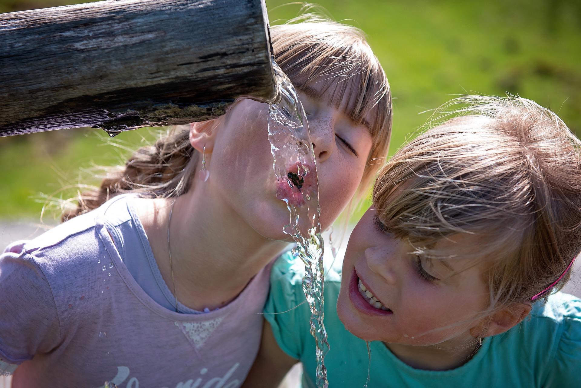 Zwei junge Mädchen trinken Wasser
