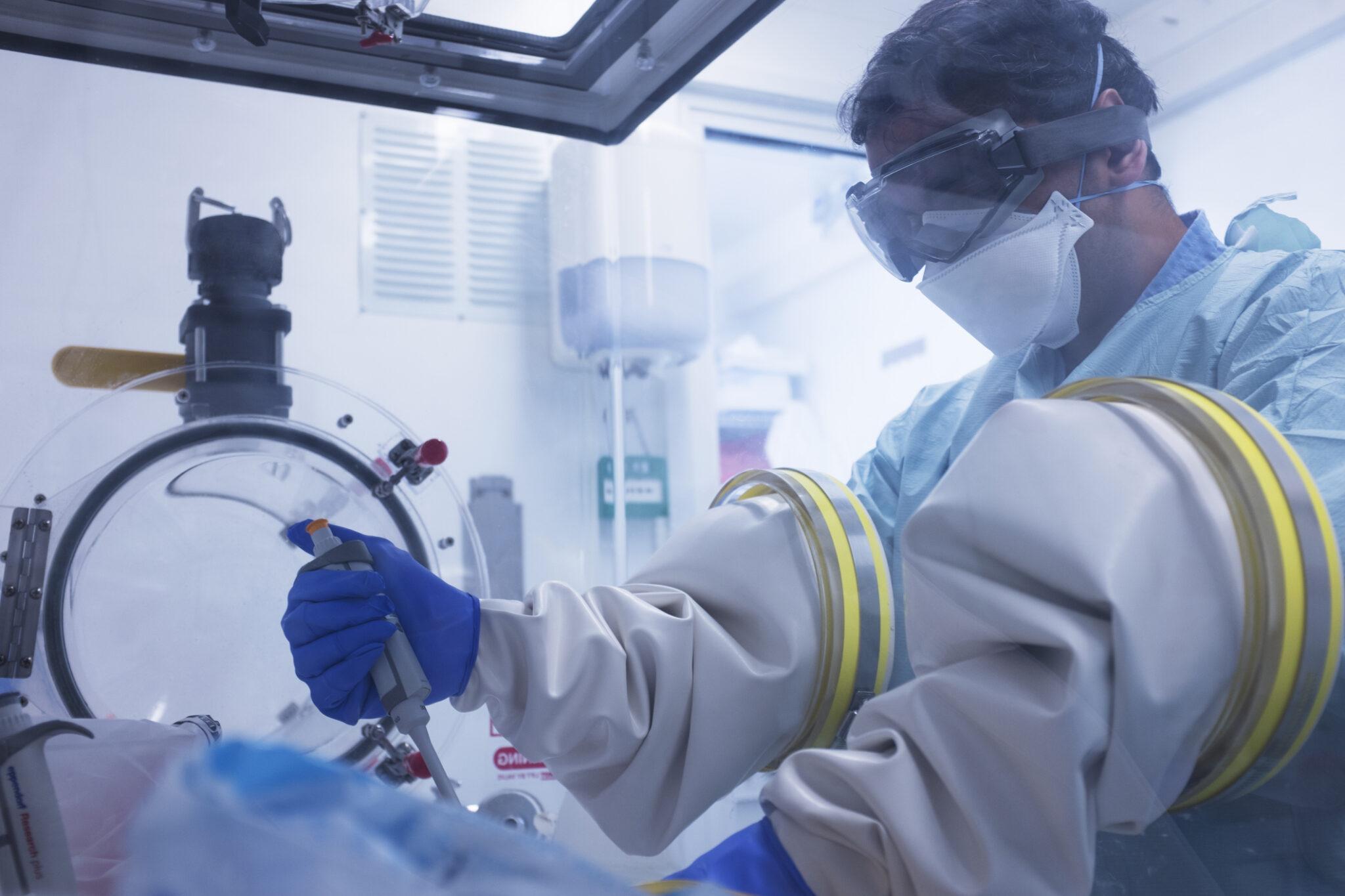 Mann mit Schutzanzug und hinter Glaswand im Labor