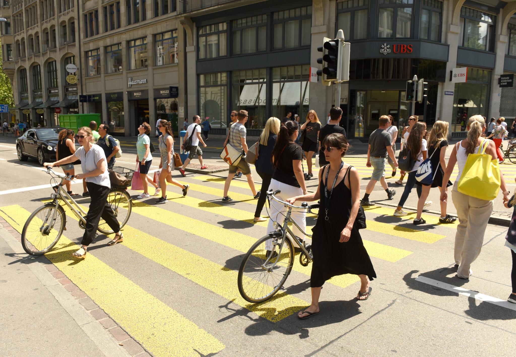 Menschen laufen über Zebrastreifen