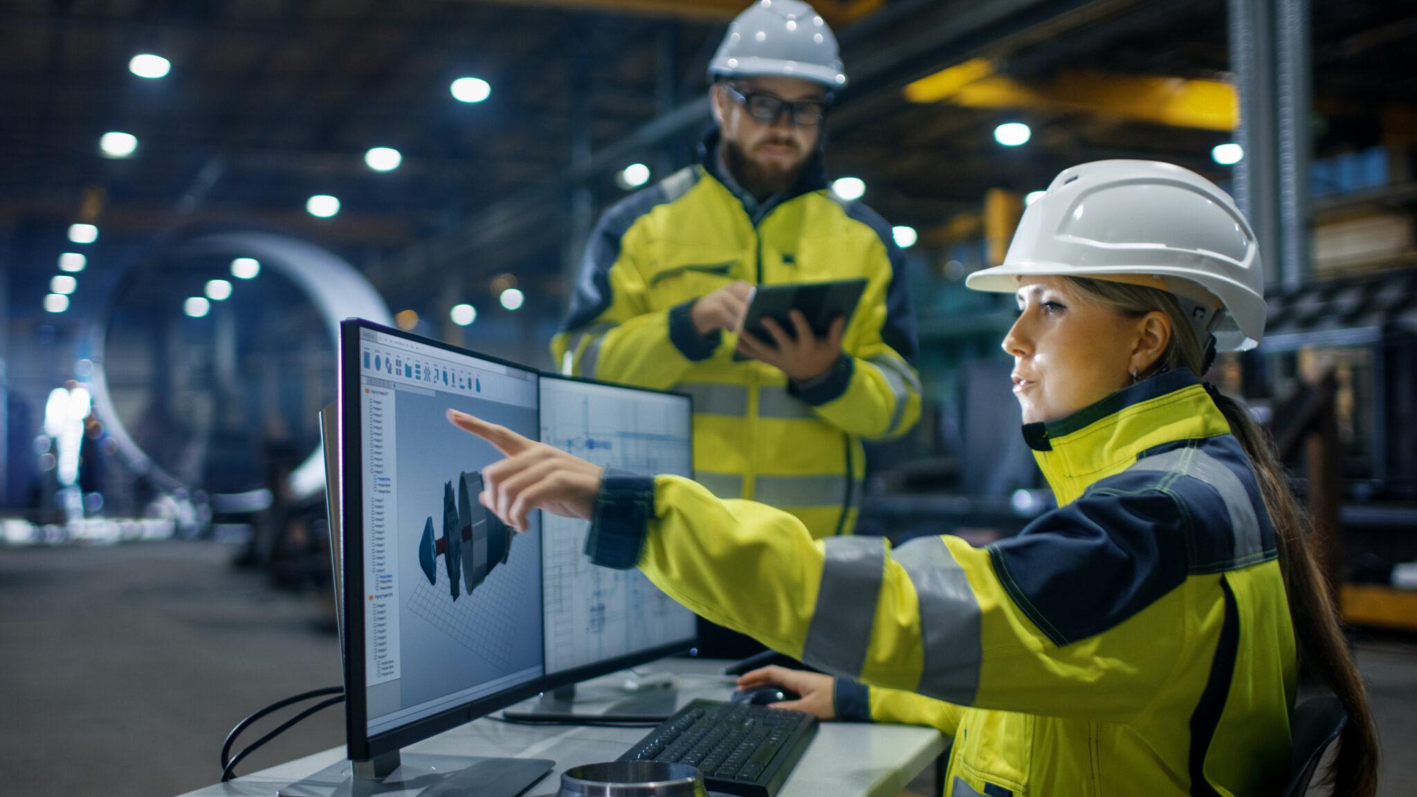 Frau und Mann in einer Fabrik. Sie am Bildschirm mit einem 3D-Modell, er am Tablet.