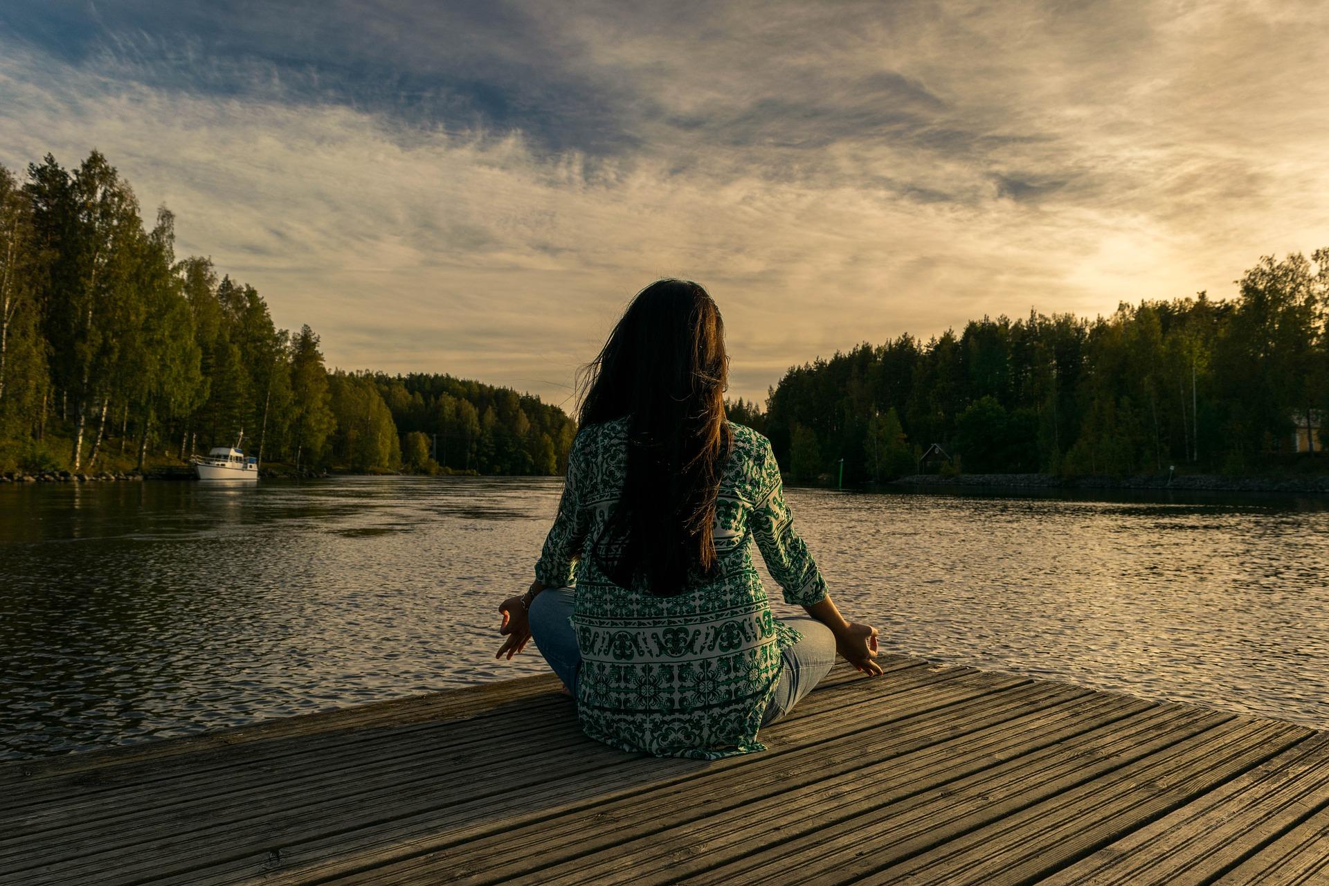 Frau in Yoga-Pose an einem See.