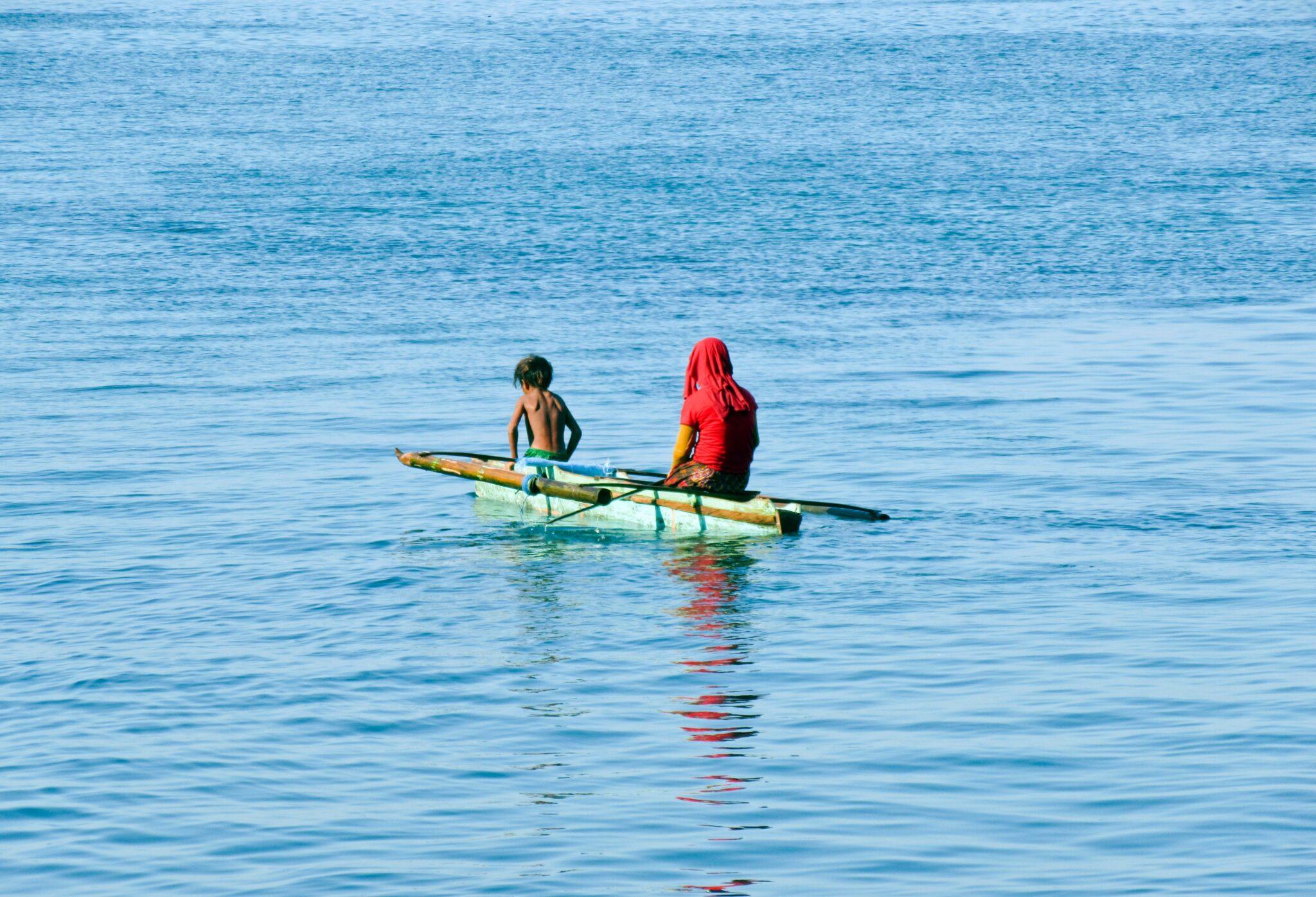 zwei Menschen, Angehörige der Bajau, in einem im Meer treibenden Boot.