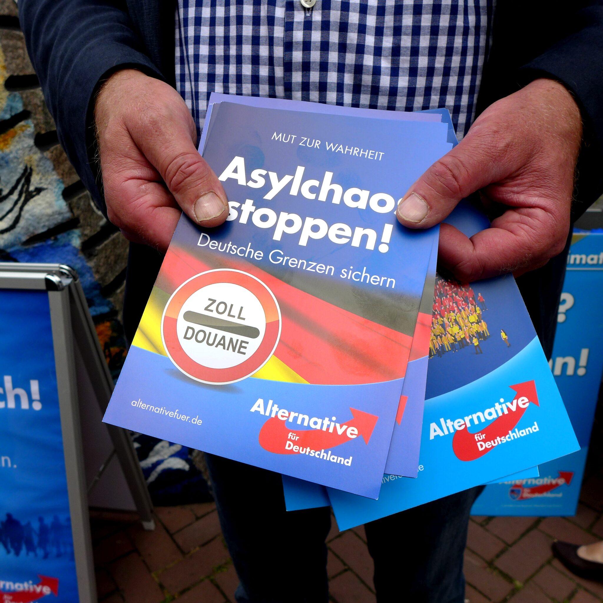 """Mann hält AfD-Flyer in der Hand mit der Aufschrift """"Asylchaos stoppen!""""."""