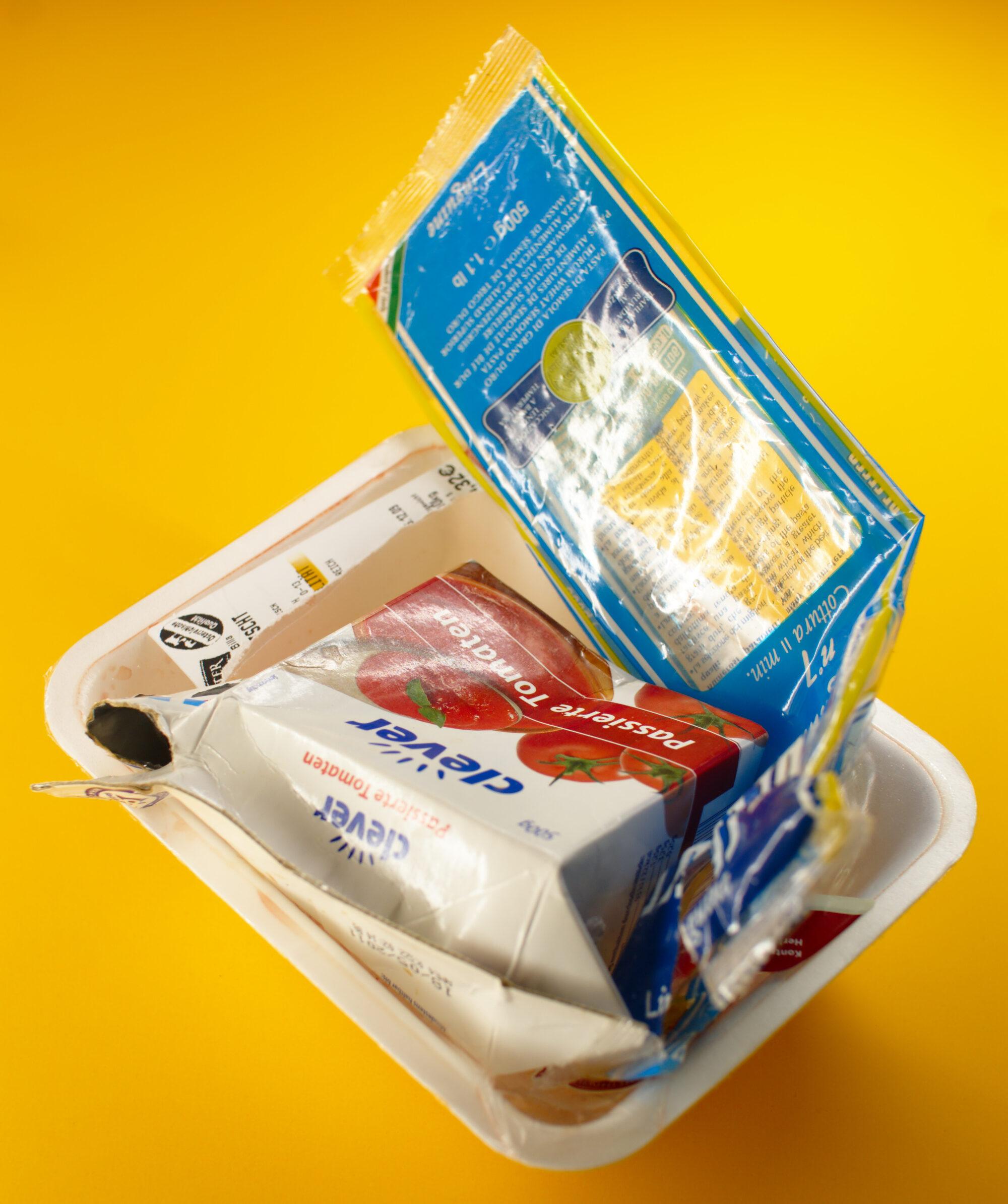 leere Lebensmittelverpackungen aus Kunststoff vor gelbem Grund.