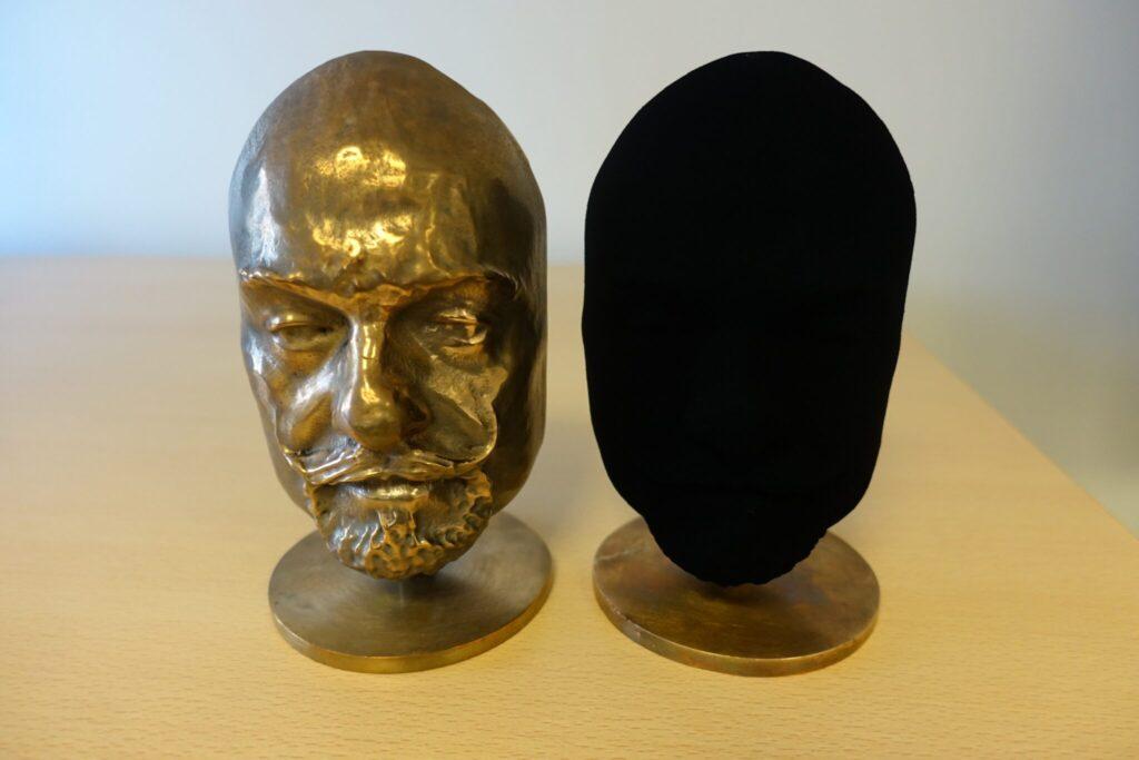 Eine mit Vantablack beschichtete Büste. Sie ist schwarz, man kann nur Umrisse erkennen.Daneben die Büste ohne Beschichtung.