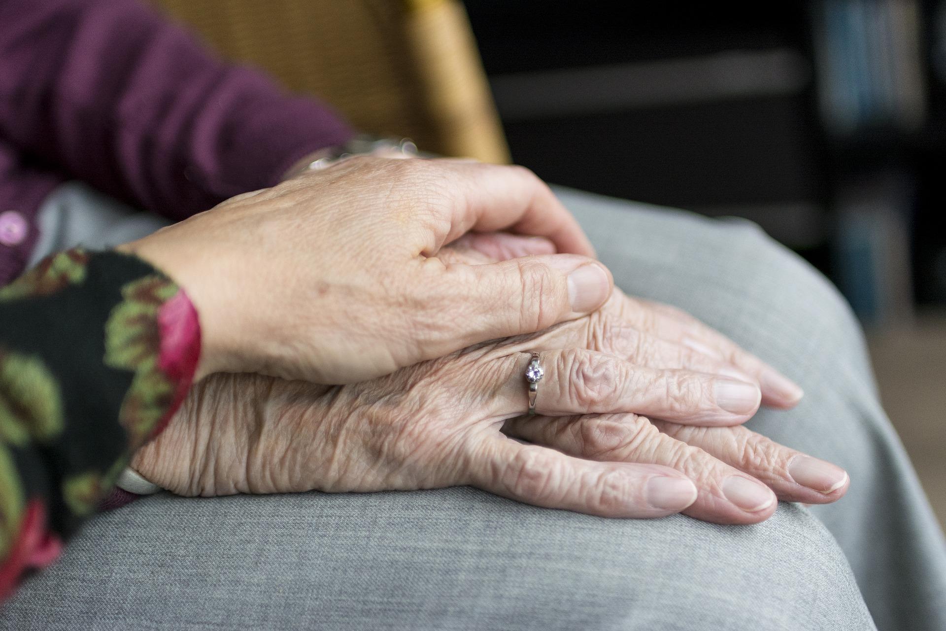 Sich haltende Hände eines älteren Paars.