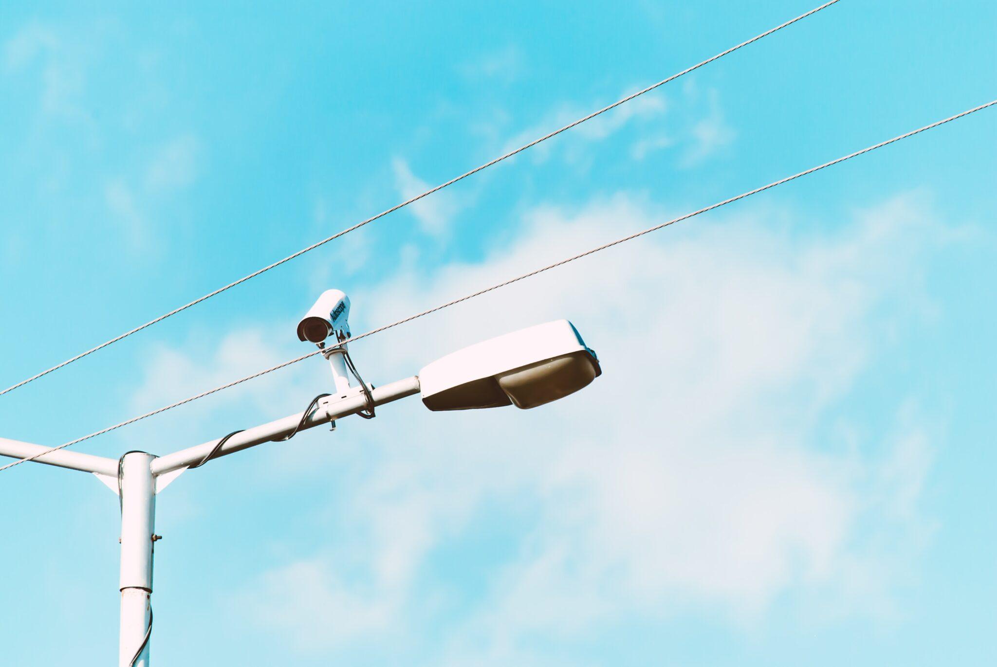 Eine Überwachungskamera, befestigt an einer weissen Strassenlaterne. Im Hintergrund der Himmel.