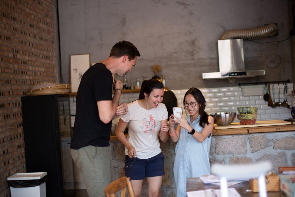 Drei Personen, die zusammen in einer Küche stehen.