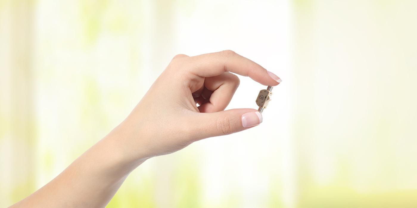 Frauenhand hält einen Samenleiterventil, isoliert auf einem weissen Hintergrund.