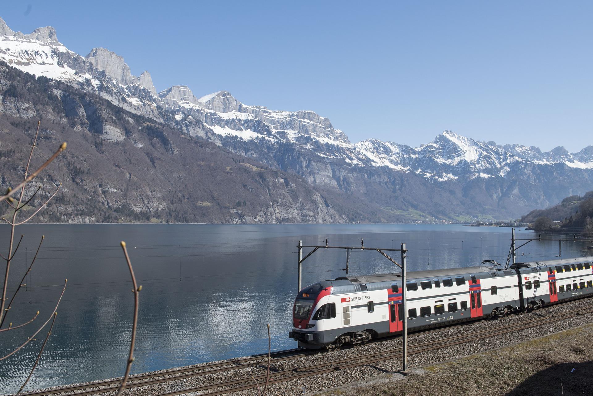 SBB-Zug vor einem See, dahinter eine Berglandschaft.