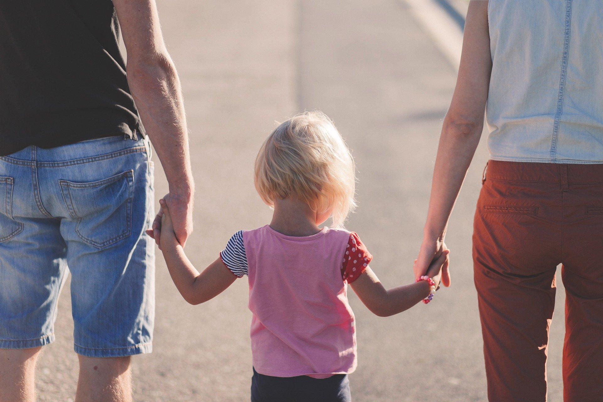 ein Kind, das von seinen Eltern an den Händen gehalten wird.