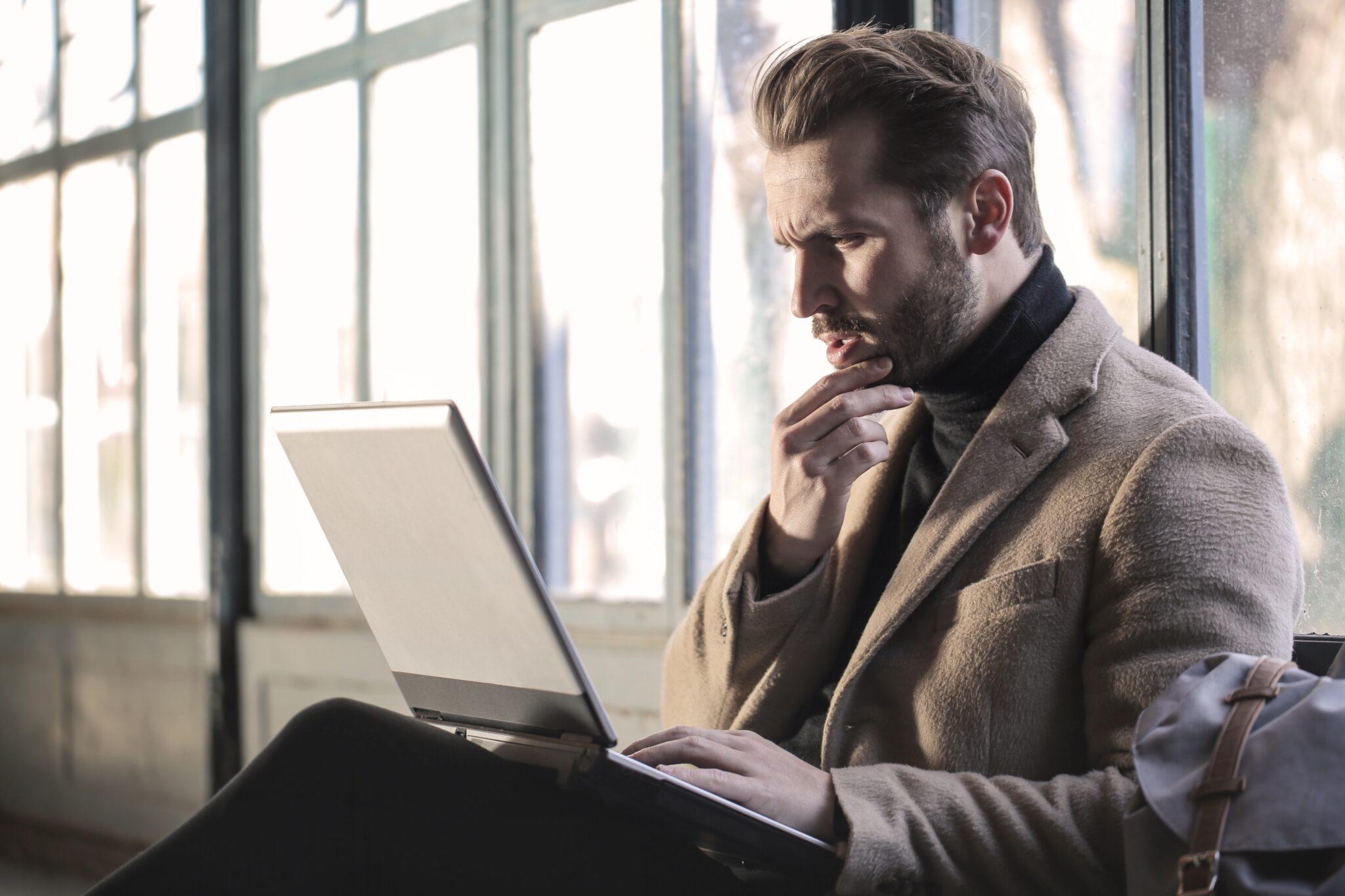 Mann schaut grübelnd auf Laptop.