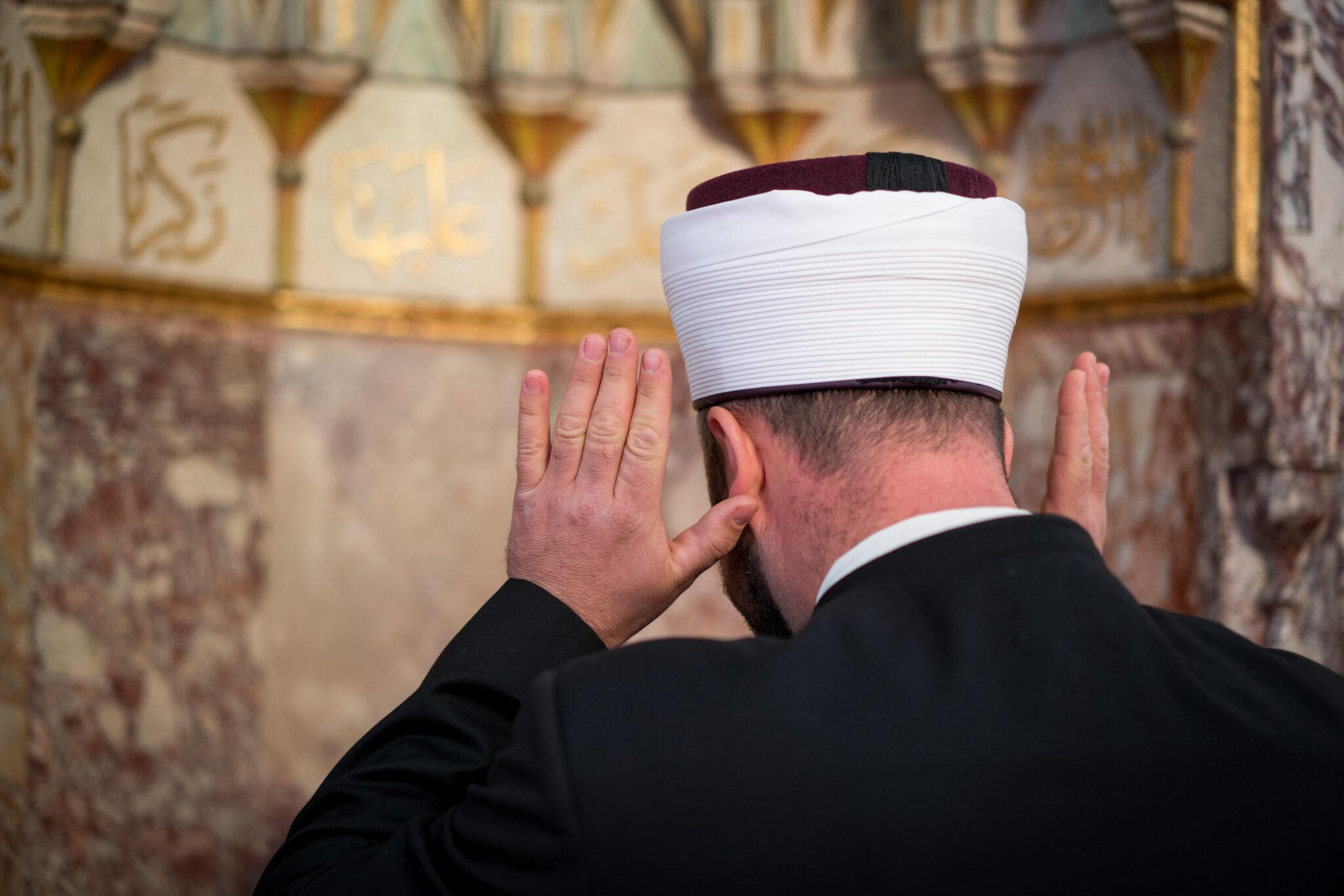 Ein Imam von hinten beim Gebet.