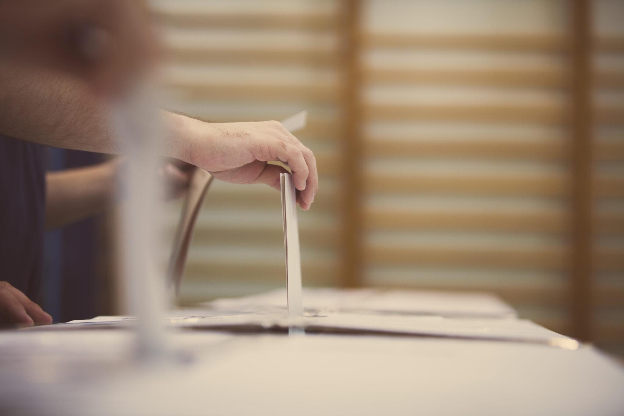 Eine Hand wirft einen Wahlzettel ein.