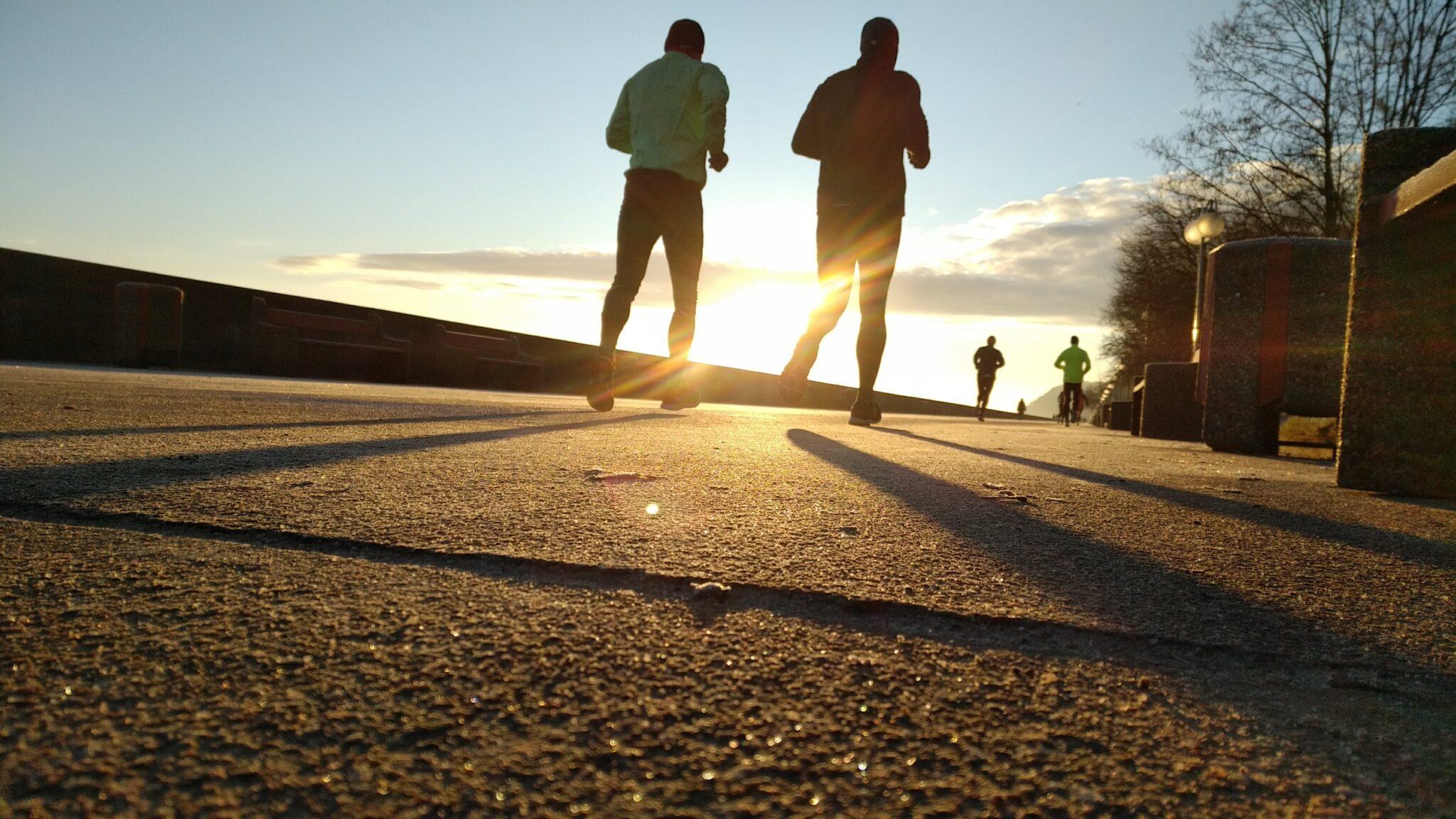 Zwei Läufer laufen der Sonne entgegen.
