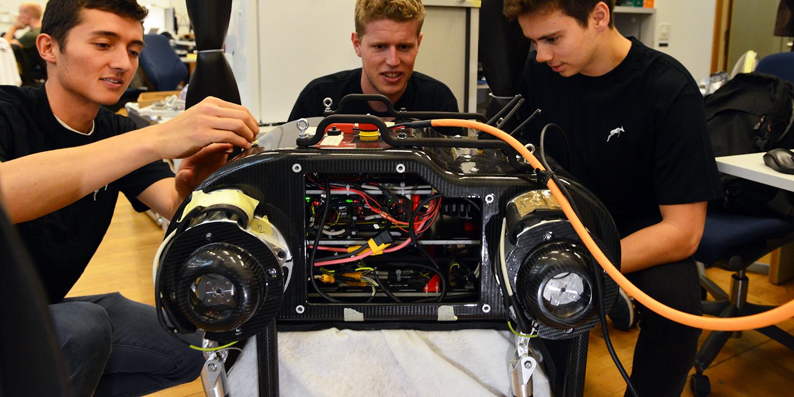 Drei Studierende knien um einen Roboter, der in der Mitte sitzt.