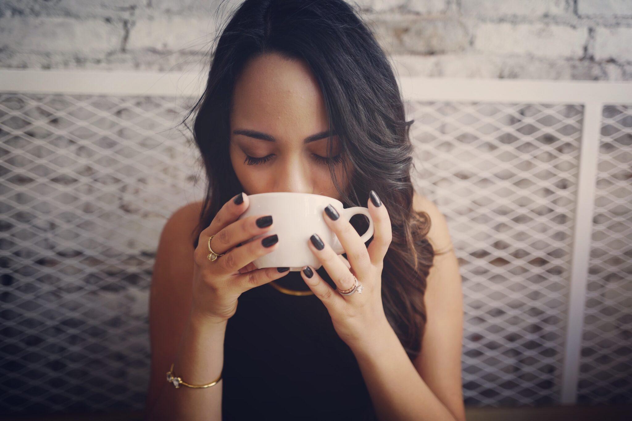 Frau trinkt aus einer weissen Tasse.