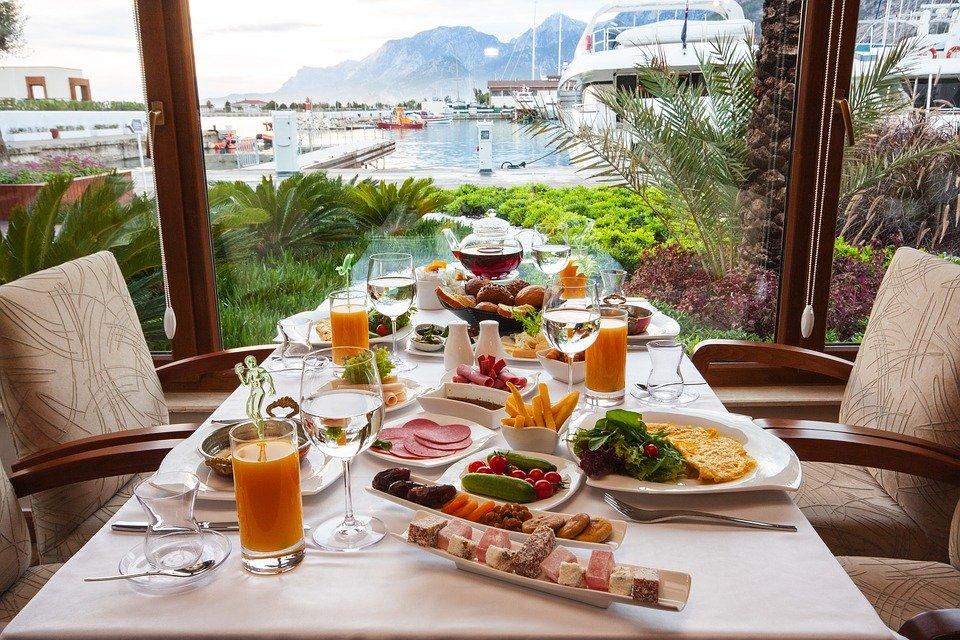 Ein reich gedeckter Frühstückstisch mit einem See, Yachten und Bergen im Hintergrund