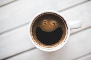 Eine Tasse Kaffee mit grinsendem Gesicht aus Schaum