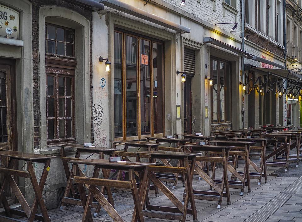 Stehtische vor einer Bar in einer Altstadt