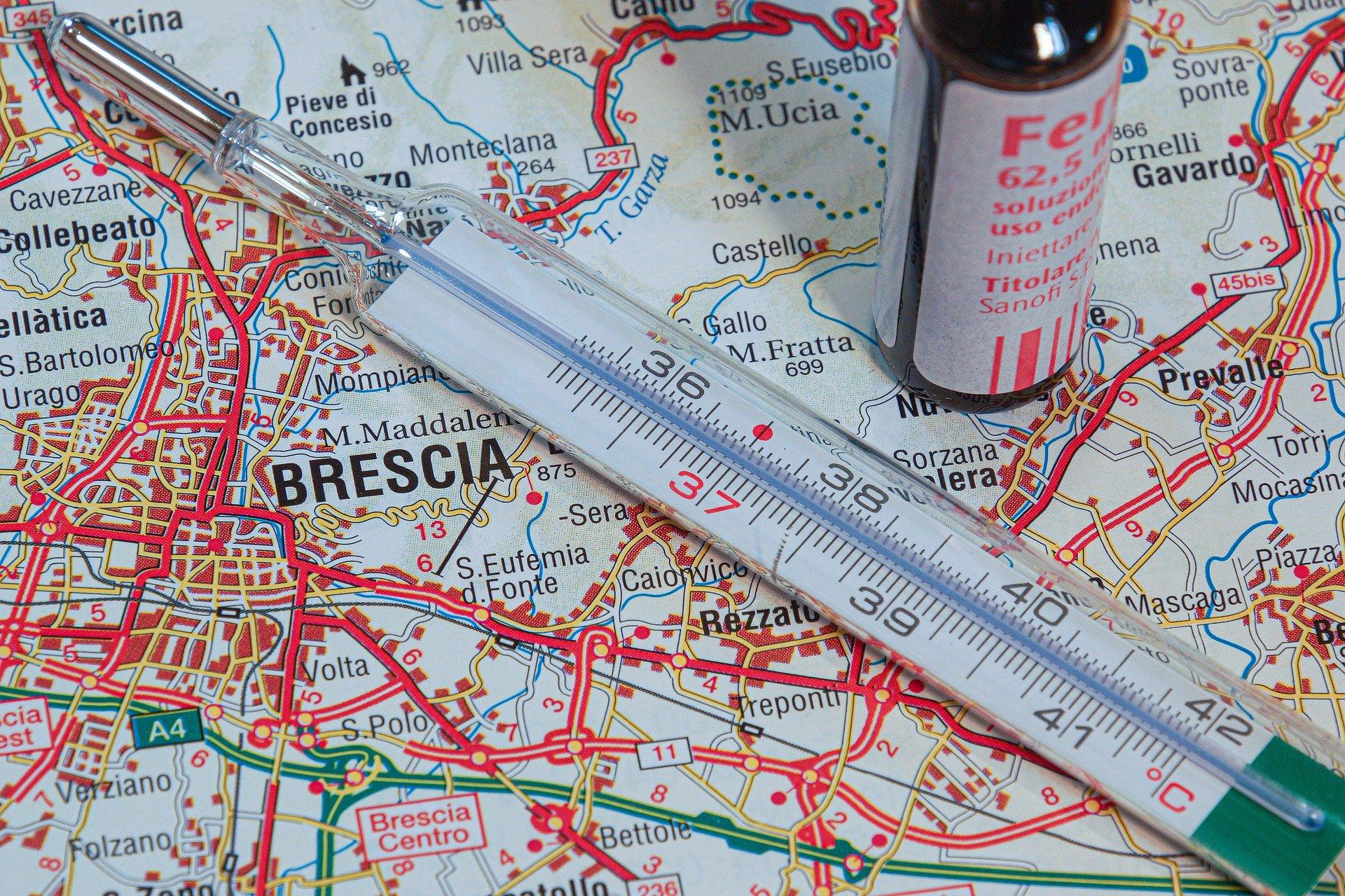 Karte von Italien mit Medizin und Fieberthermometer daraufgestellt