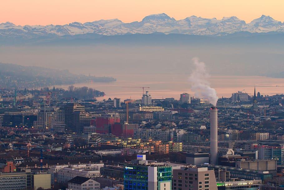 Zürcher Stadtpanorama mit rauchendem Industrieschornstein und Smog