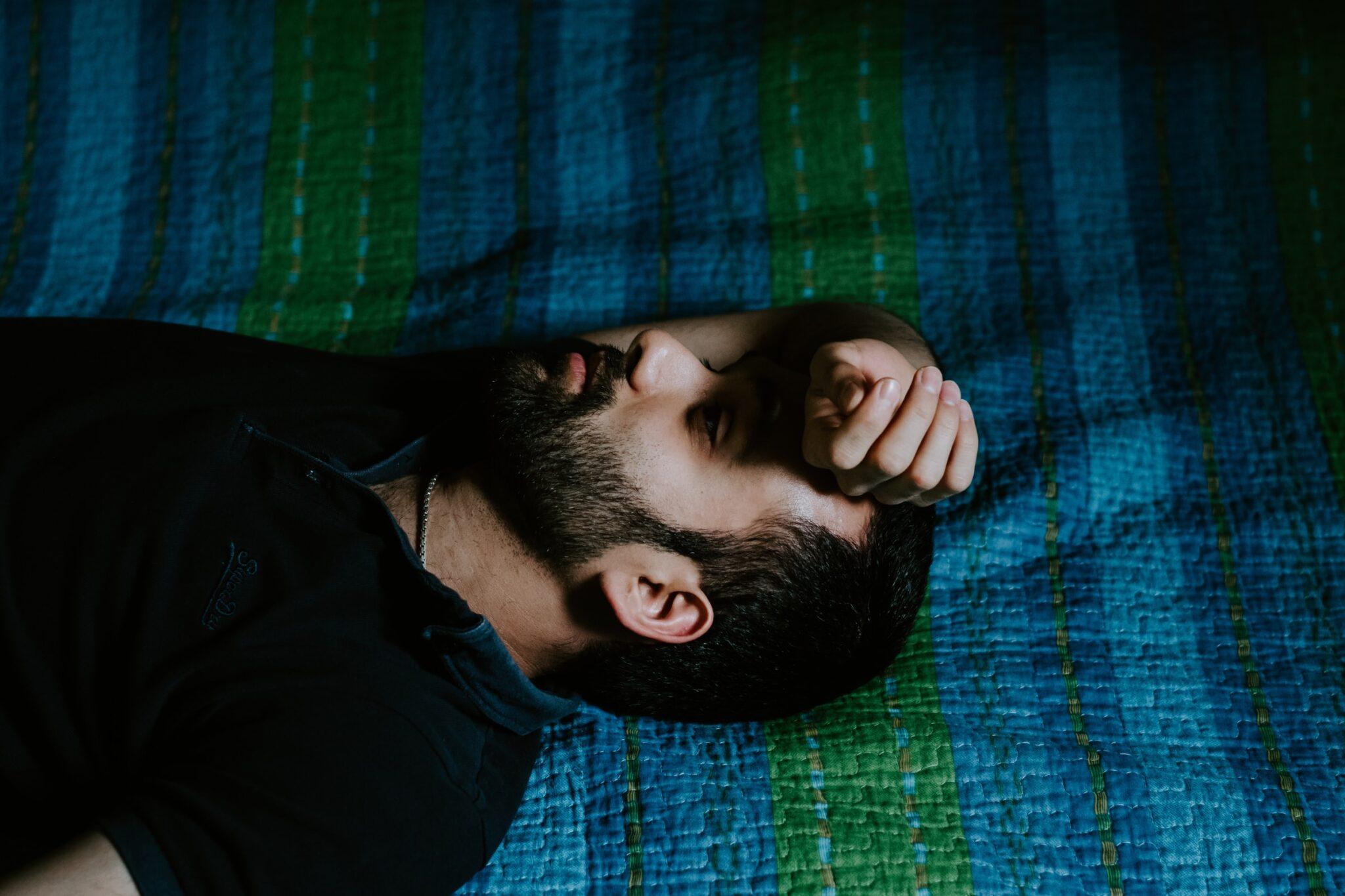 trauriger oder gelangweilter Mann liegt rücklings auf dem Bett