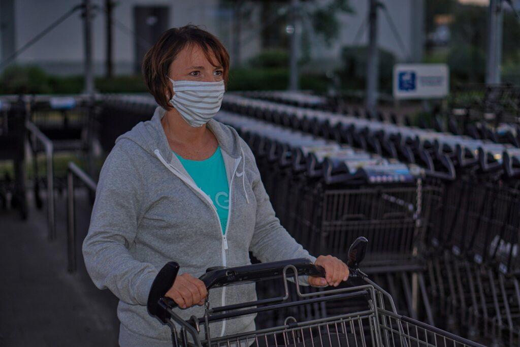 Frau mit selbstgenähter Gesichtsmaske schiebt einen Einkaufswagen