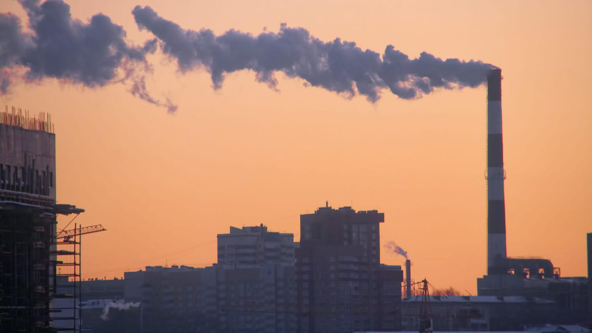 Industrieschornstein mit Rauchschwade vor orangenem Himmel