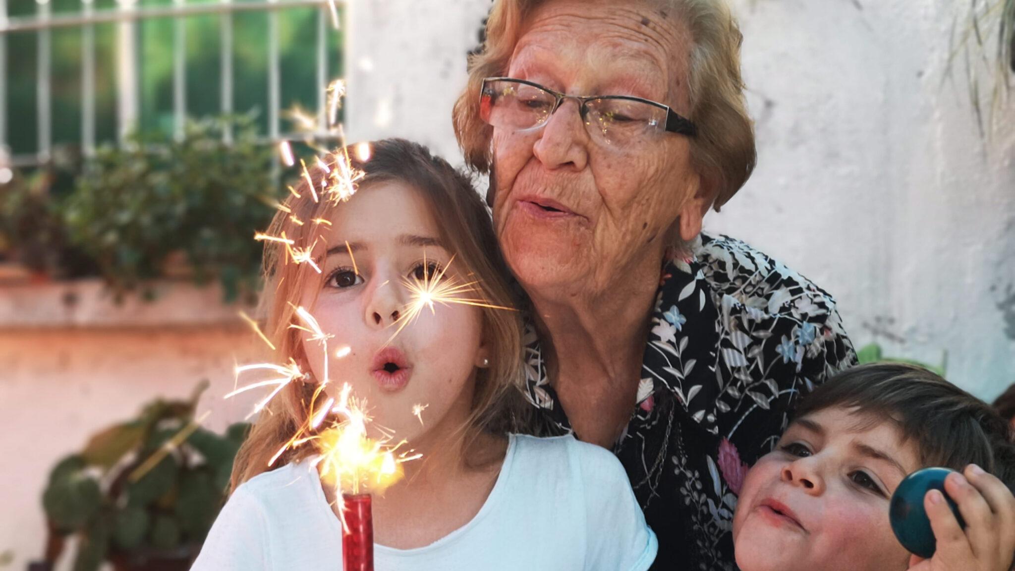 Kindergeburtstag mit brennender Kerze, Kindern und einer Grossi