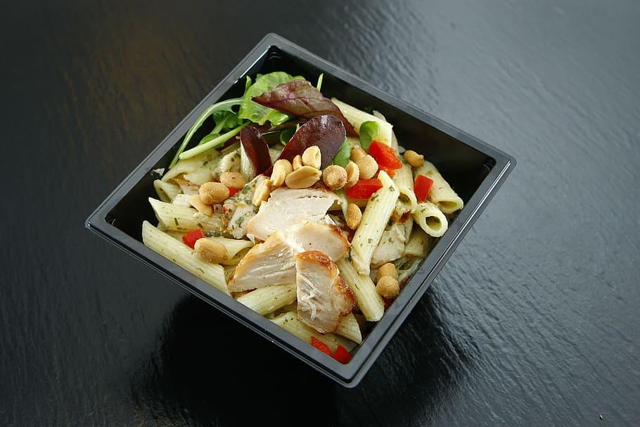 Take-Away Gericht mit Nudeln, Pulet und Erdnüssen in einer schwarzen quadratischen Plastikschale.