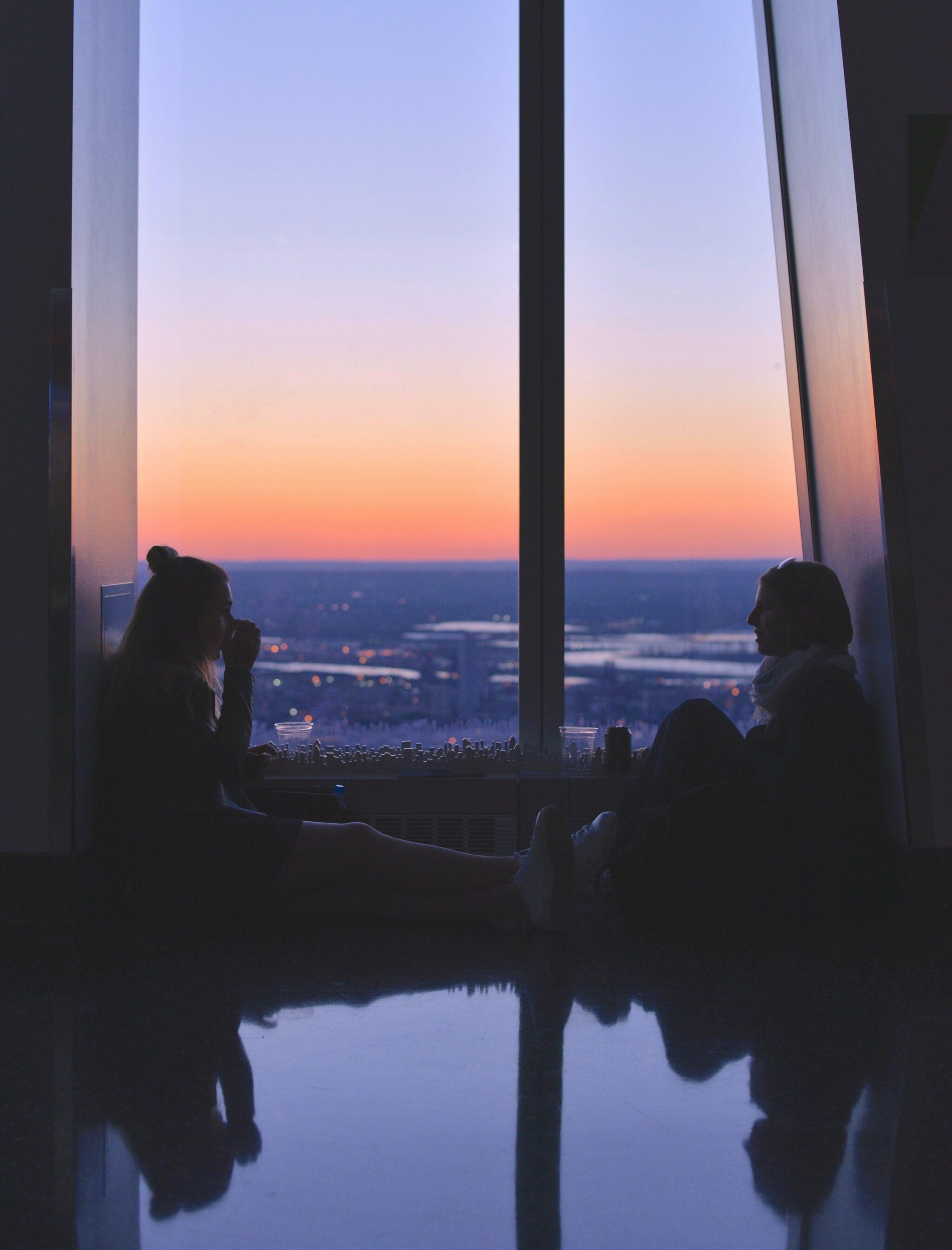 2 Frauen sitzen auf dem Boden vor einem Sonnenuntergang über einer Stadt