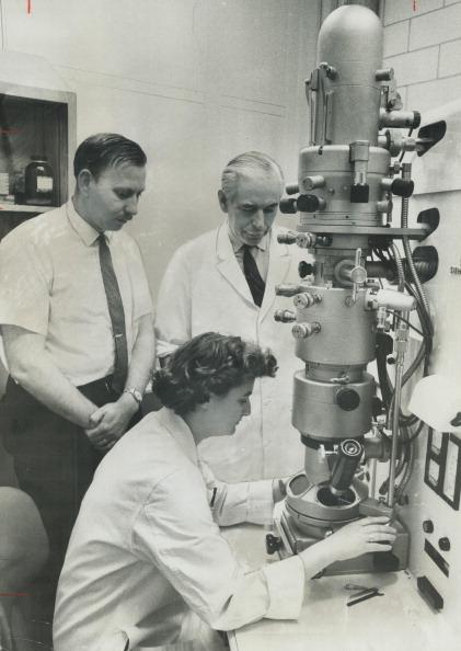 June Almeida am Elektronemikroskop, hinter ihr 2 Männer.