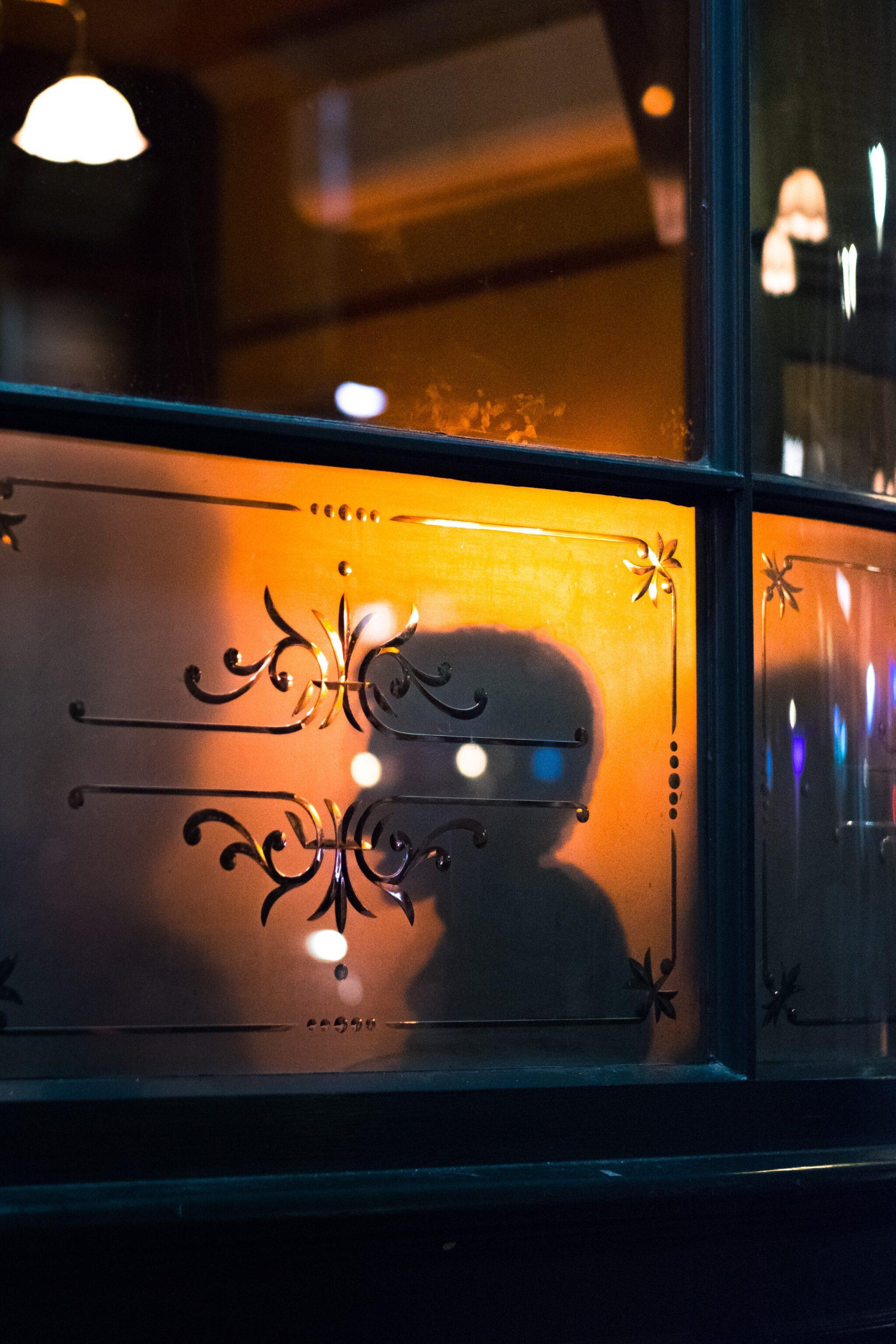 Schattenumriss eines Menschen mit Lichtreflexen, die wie augen aussehen, hinter einer Milchglasscheibe einer Bar