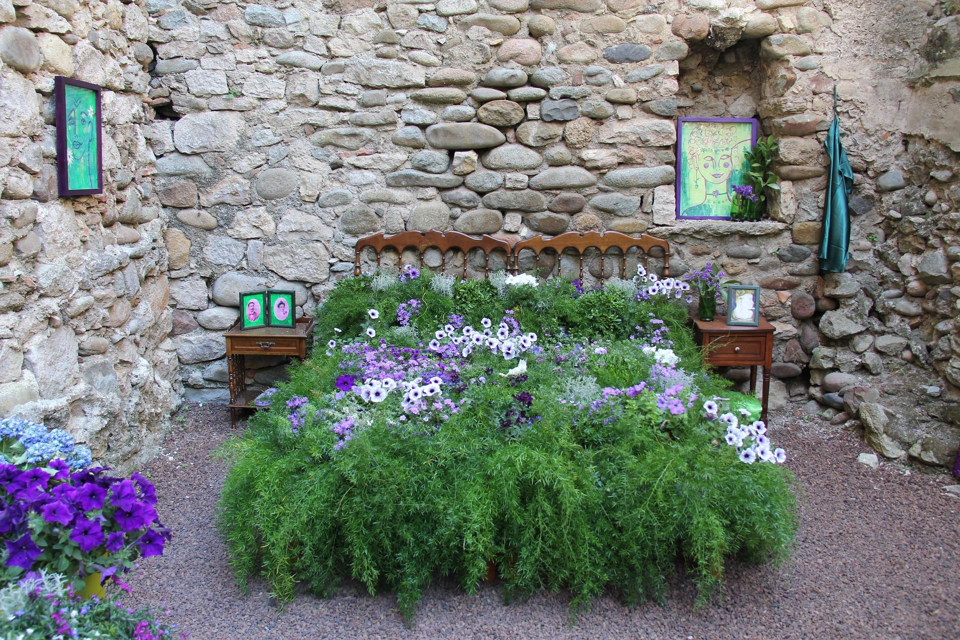 Ein vor einer Steinmauer in einem Garten nachgebildetes Schlafzimmer mit Beet als Bett mit viel Grün und einigen lila Blumen.