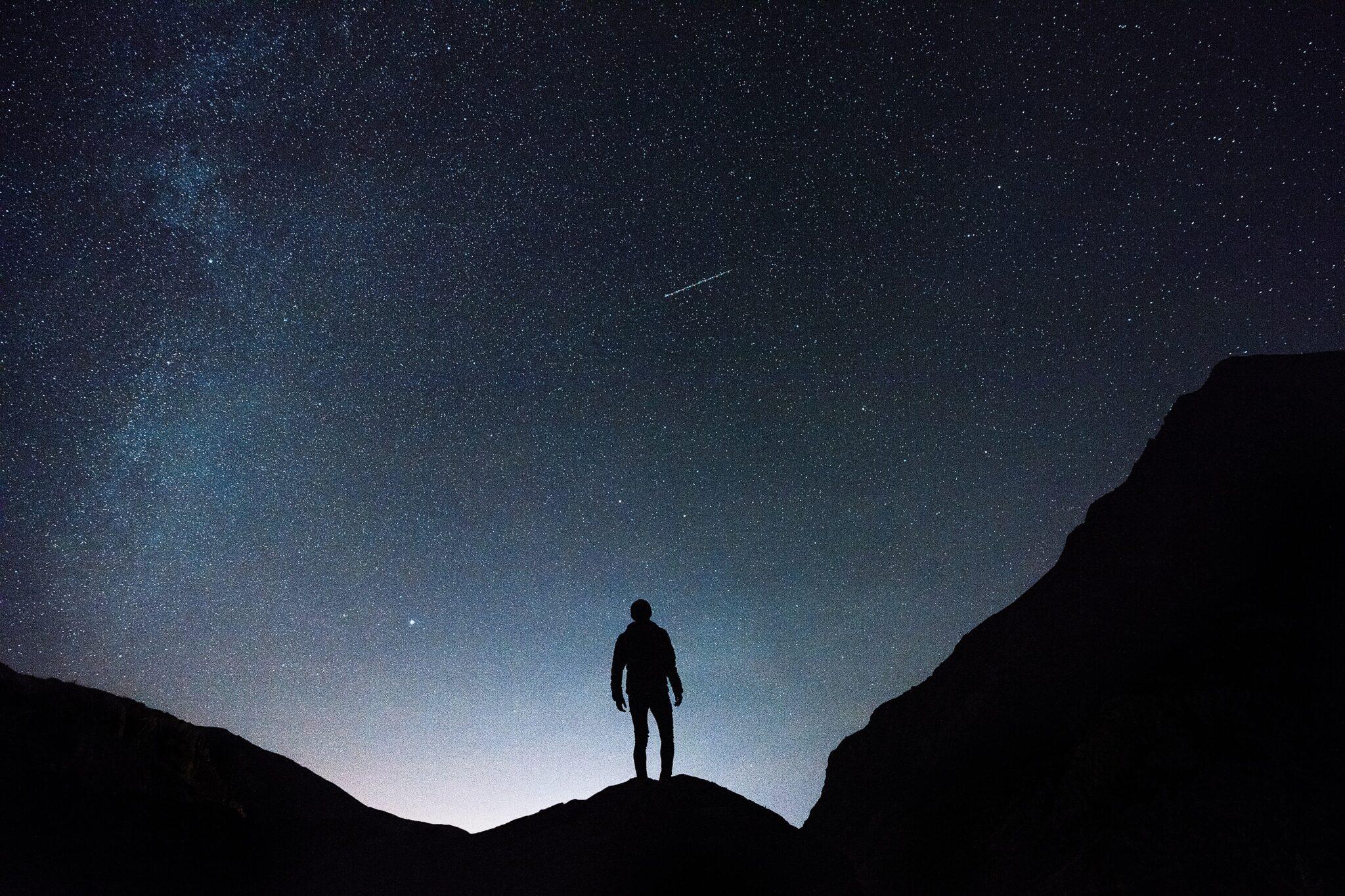 Ein Mensch steht unter dem Sternenhimmel und schaut auf einen Kometenschweif