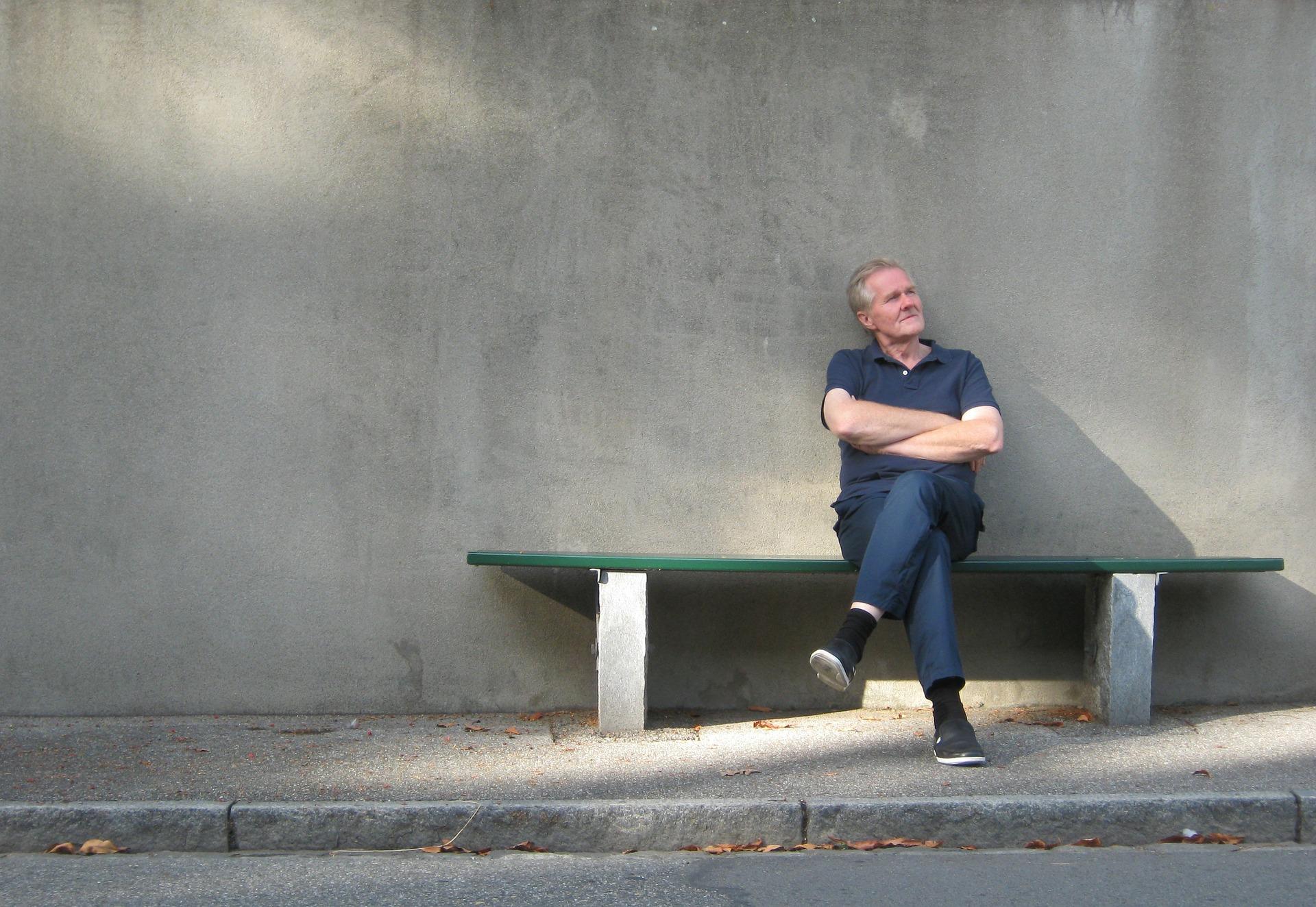 Ein Mann sitzt entspannt auf einer Bank und tut nichts.