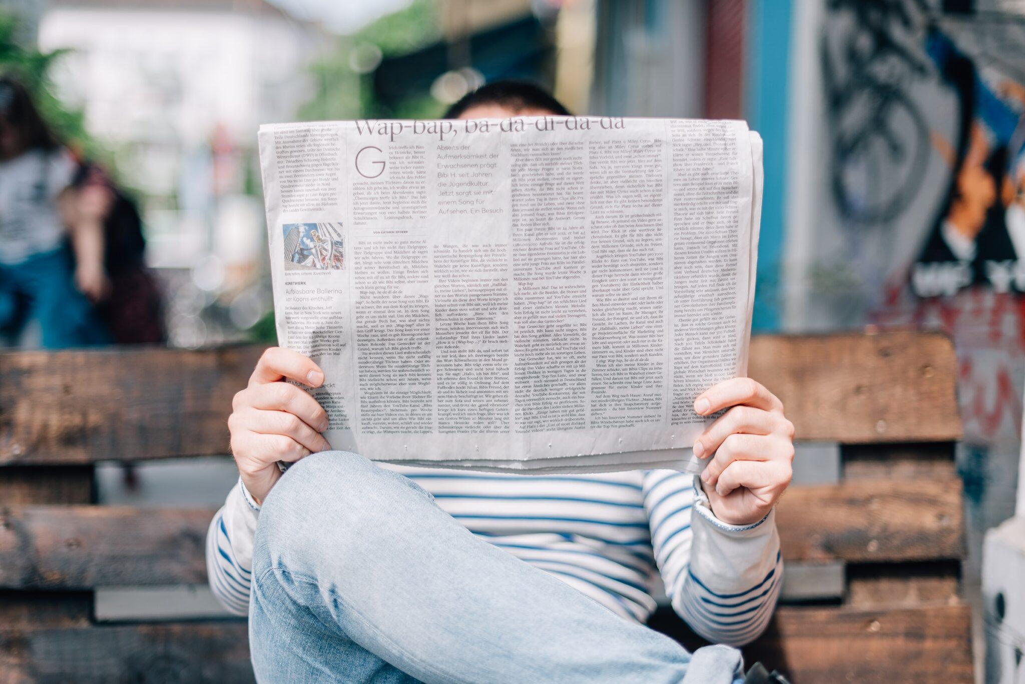 Ein Mann liest auf einer Holzbank eine Zeitung