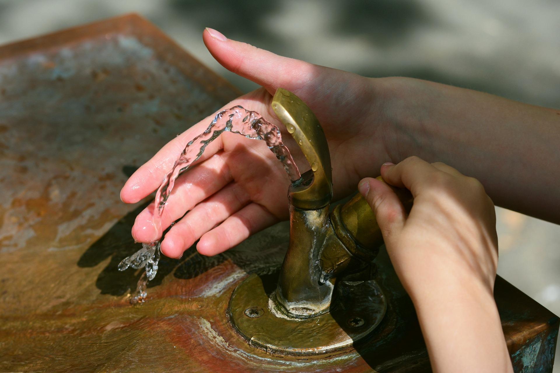 2 Hände an einem Trinkwasserbrunnen