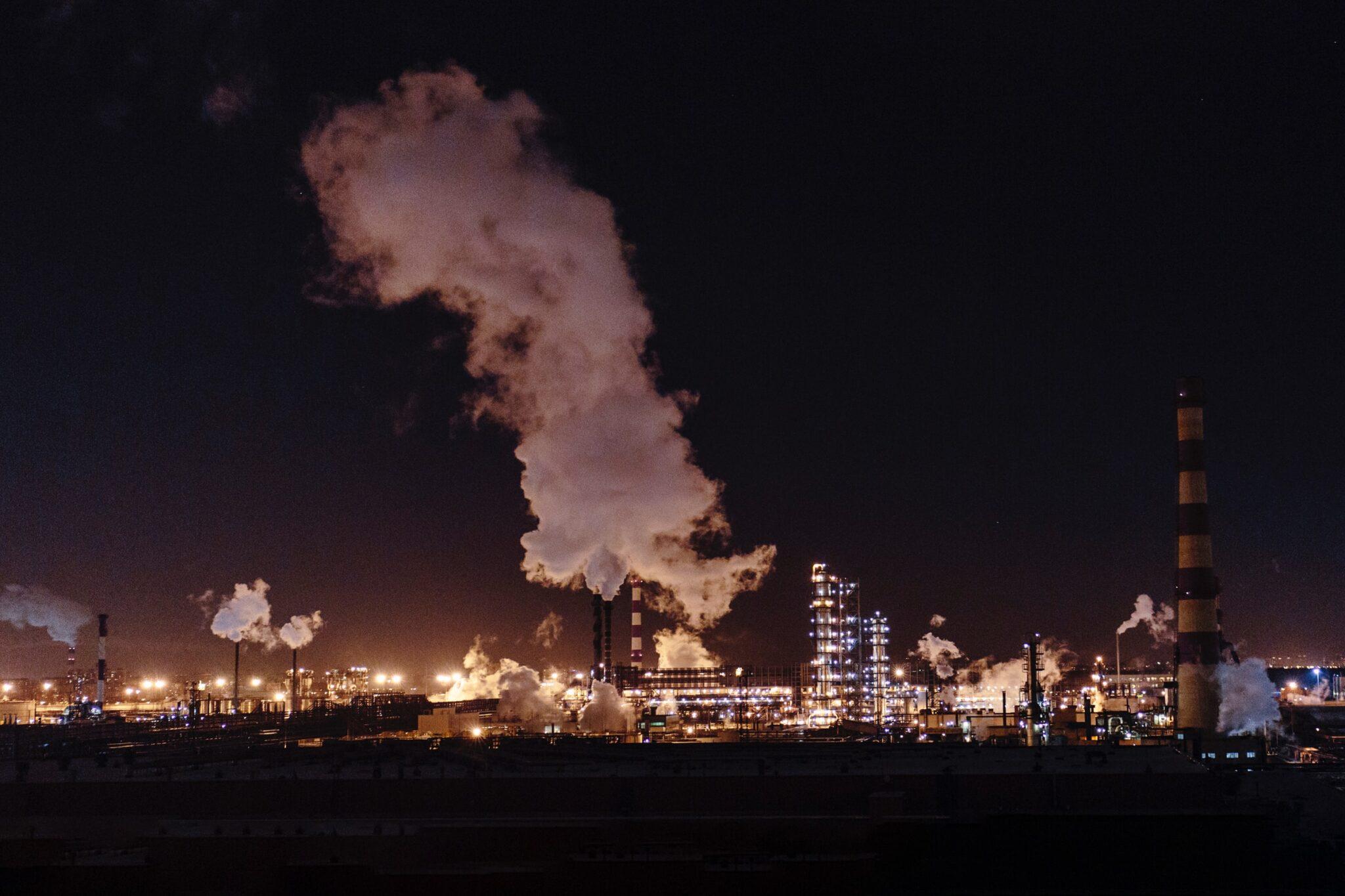 Fabriklandschaft mit viel Rauch bei Nacht mit viel Beleuchtung