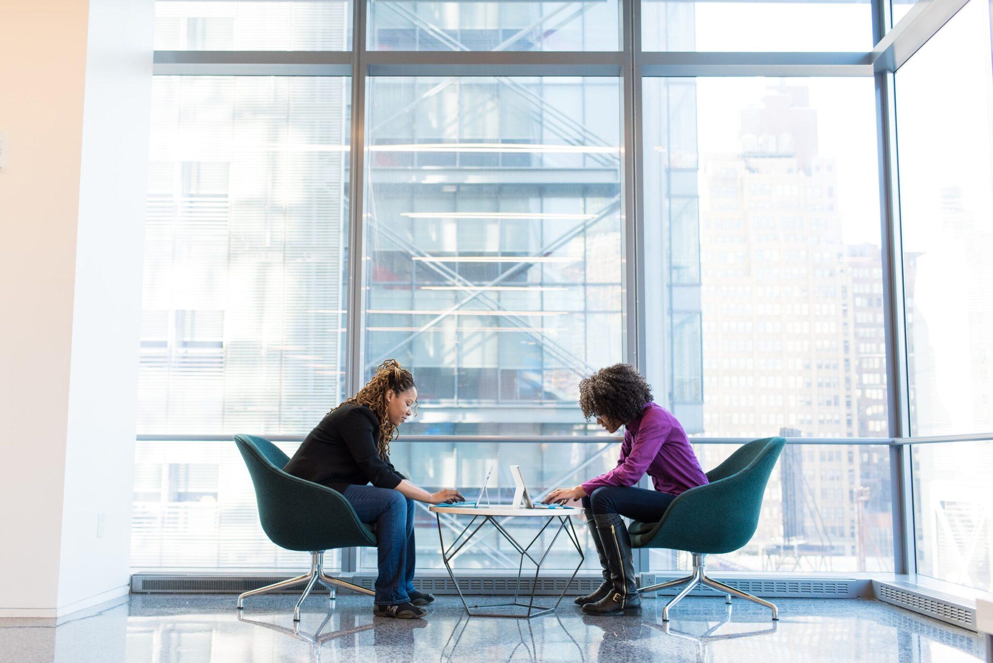 2 Frauen sitzen recht krumm über Laptops gebeugt an einem Cafétisch