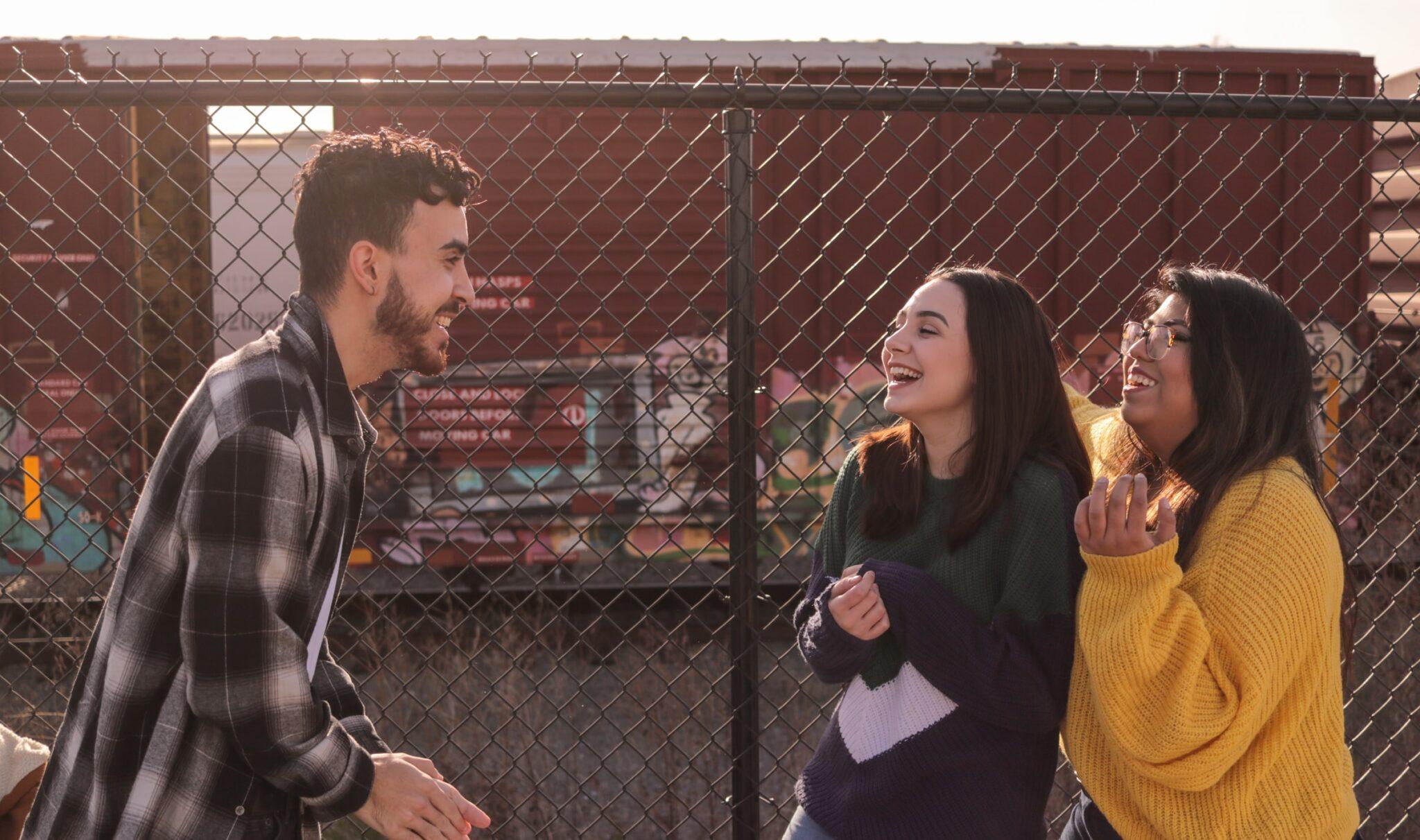 Ein Mann erzählt etwas lustiges, worüber 2 Frauen lachen. Sie stehen draussen, im Hintergrund ist ein Maschendrahtzaun zu sehen.
