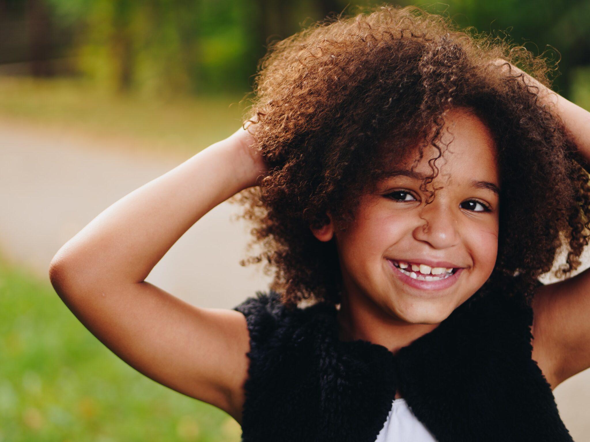 Mädchen mit Afro-Locken greift sich auslandend mit beiden Händen in die Haare und strahlt