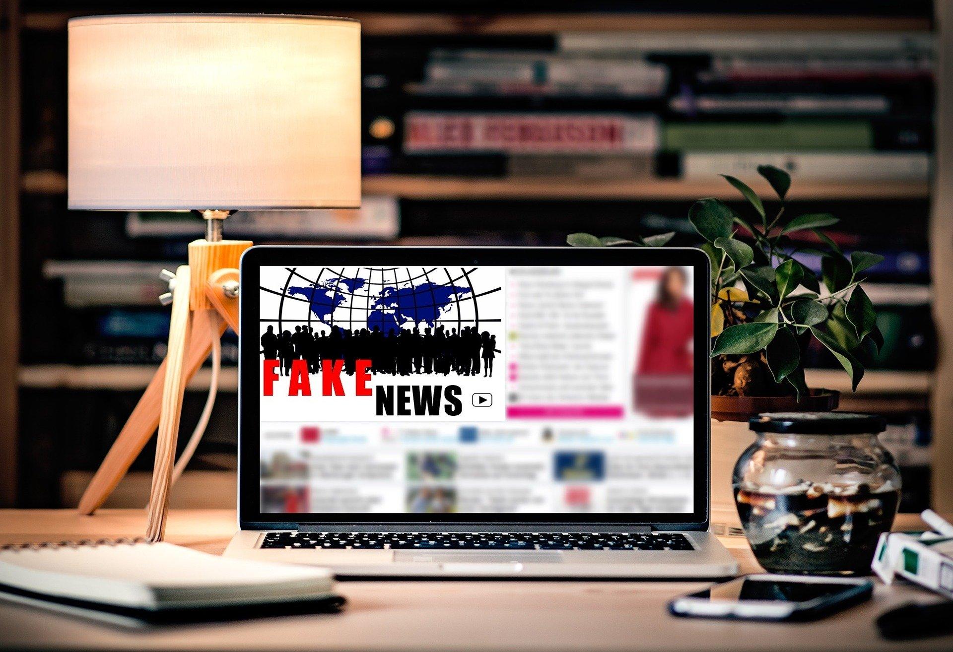 EIn Tablet steht auf einem Schreibtisch und zeigt eine Fakenews Website an.